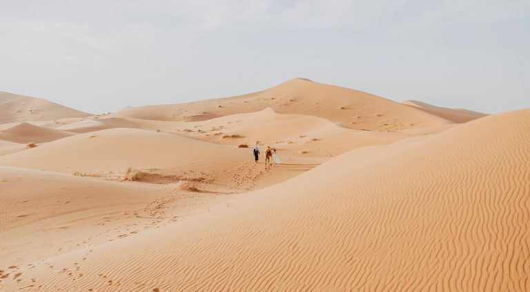 Sahara desert in Erg Chebbi Based in Morocco with two people walking in the landscape