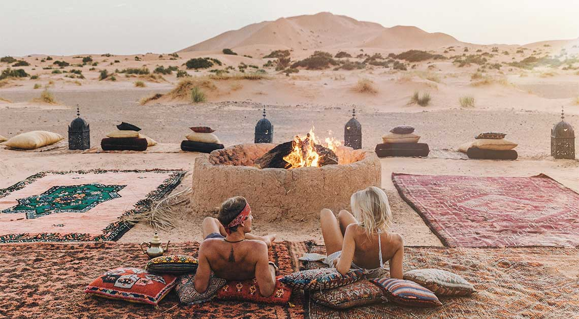 Two influencers looking the Sahara desert of Merzouga in Morocco around the firepit in a camp.