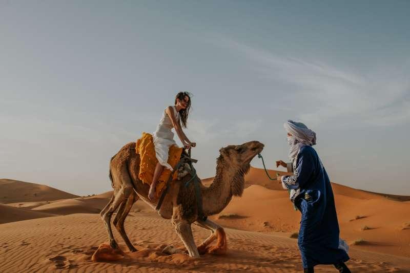 Chica en una excursion en camello en el desierto del Sahara de Marruecos, con un bereber nativo ayudandola.